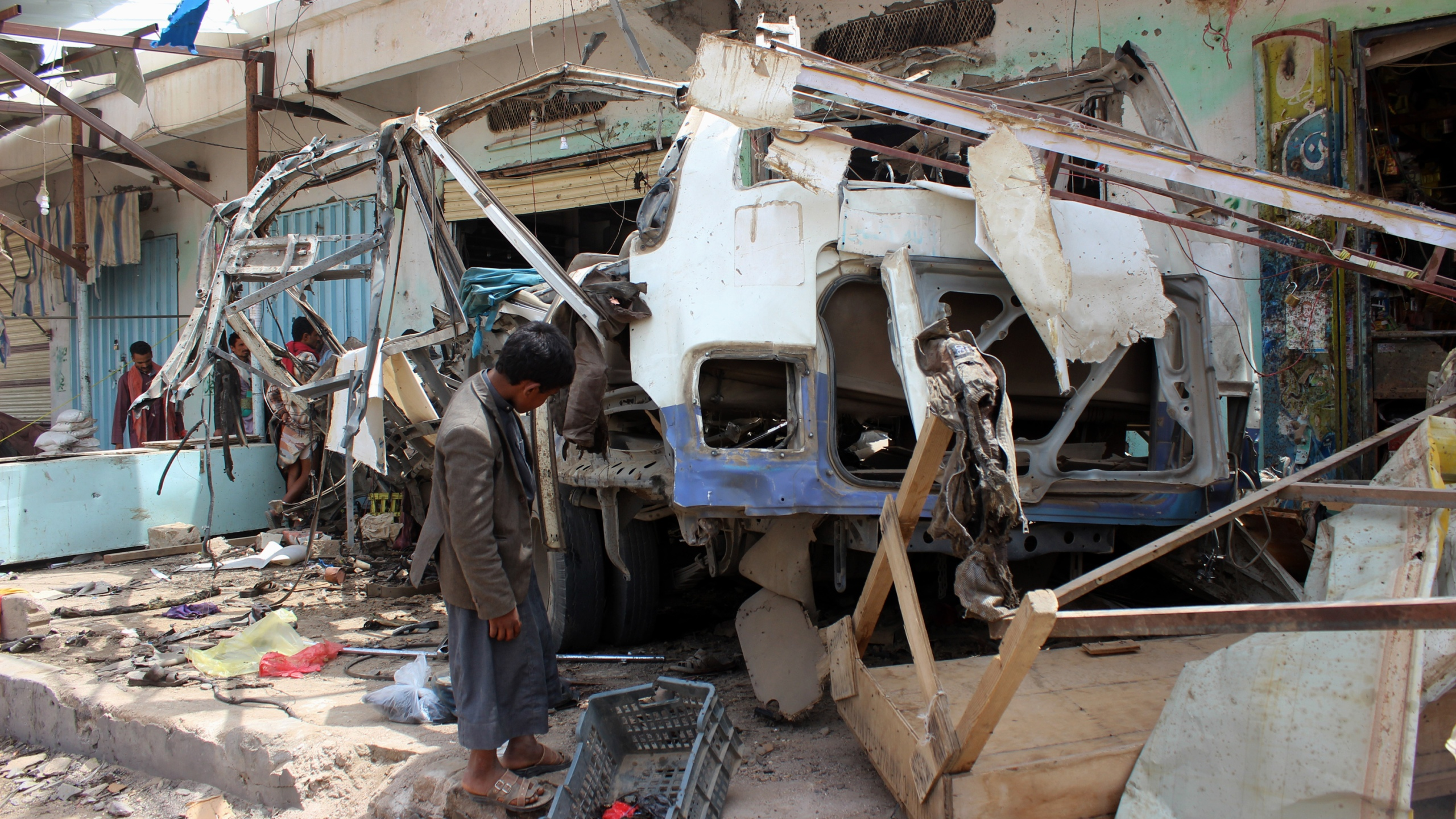 A Yemeni child stands next to the destroyed bus at the site of a Saudi-led coalition air strike, that targeted the Dahyan market the previous day in the Huthi rebels' stronghold province of Saada on August 10, 2018. (Credit: STRINGER/AFP/Getty Images)