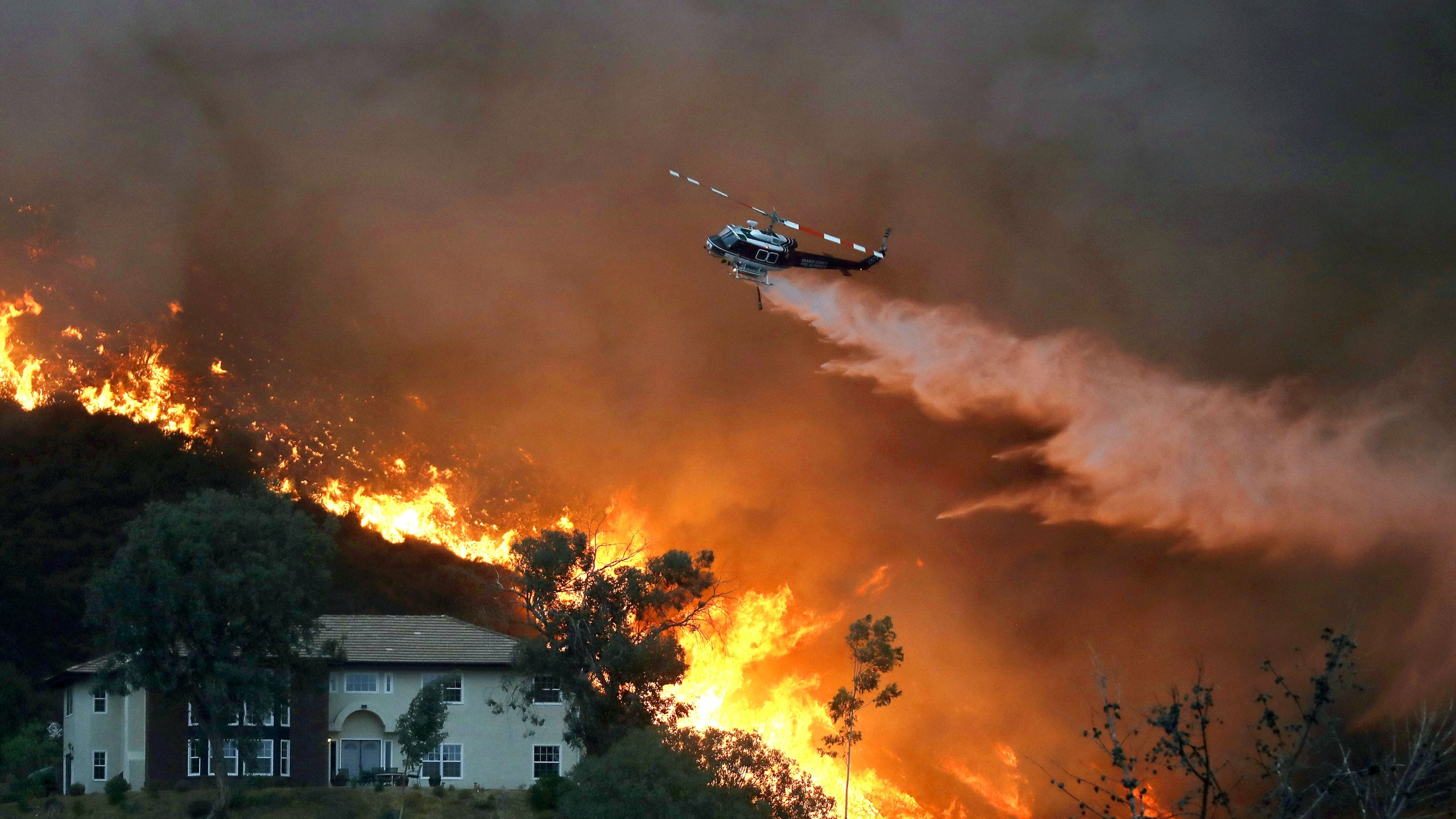 A firefighting helicopter makes a water drop as the Holy Fire burns near homes in Lake Elsinore on Aug. 9, 2018. (Credit: Mario Tama / Getty Images)