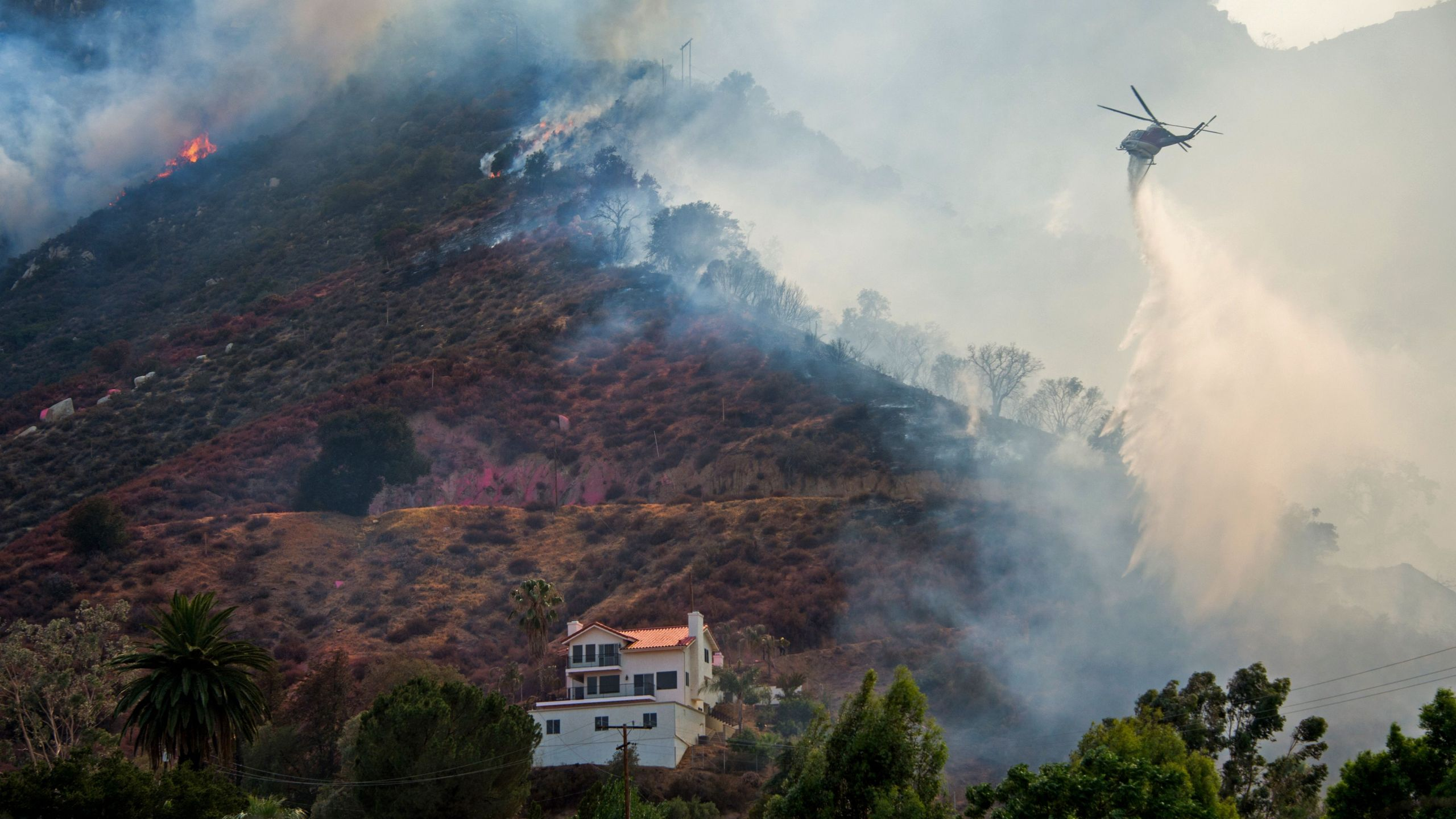 A helicopter drops water to protect a home from the Holy Fire in Lake Elsinore, California on Aug. 10, 2018.(Credit: ROBYN BECK/AFP/Getty Images)