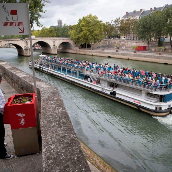 A man stands at a 'uritrottoir' public urinal on August 13, 2018, on the Saint-Louis island in Paris, as a 'bateau mouche' tourist barge cruises past. (Credit: THOMAS SAMSON/AFP/Getty Images)