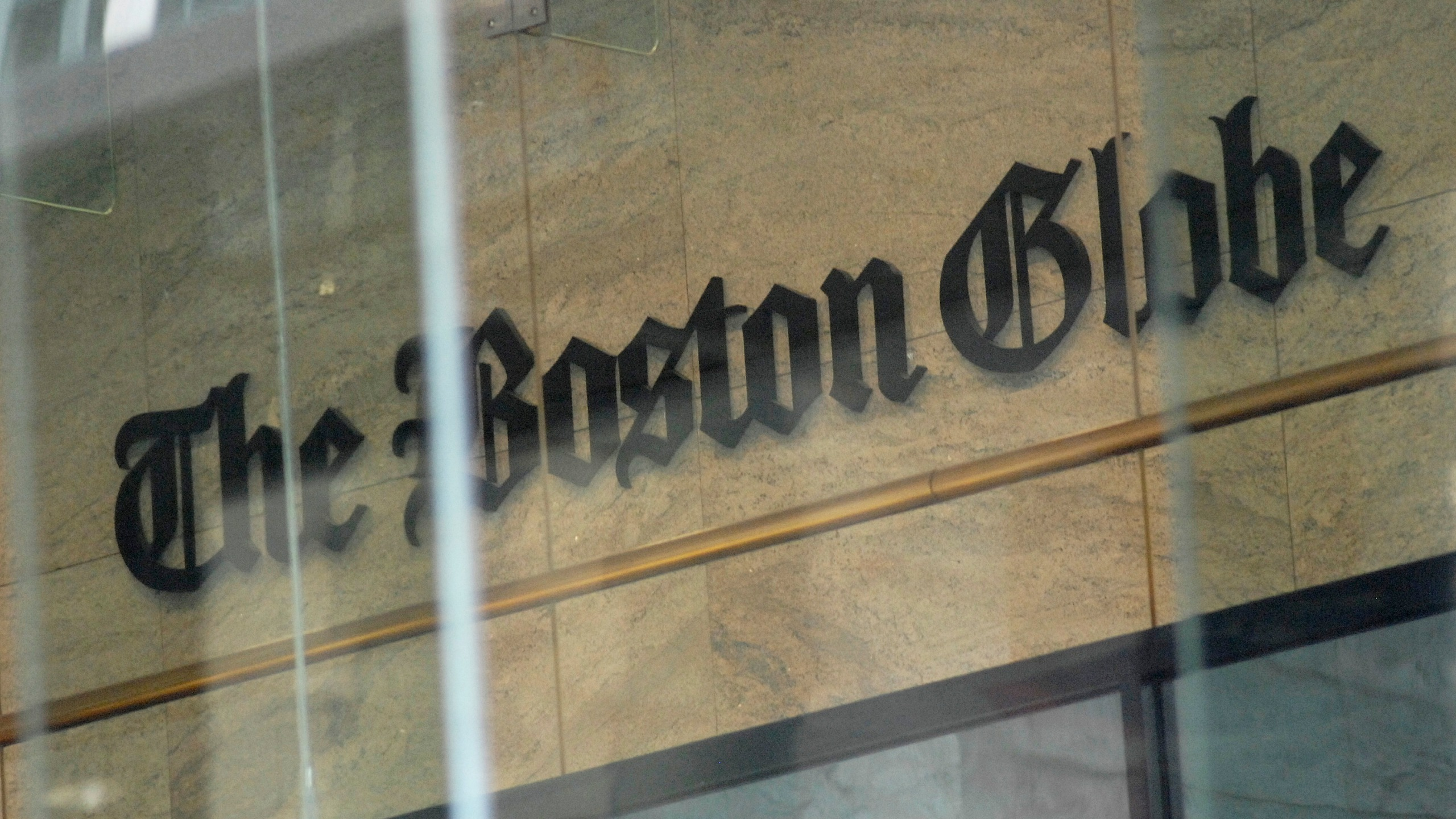 """The Boston Globe logo as seen through the windows across from the new location of the Boston Globe at 53 State Street, Boston, at one Exchange Place in the Exchange Building on August 15, 2018. - Branded """"enemy of the people"""" by us President Donald Trump, the US news media is responding with a campaign aimed at countering the president's narrative and highlighting the importance of a free press. More than 200 news organizations are to participate in a coordinated campaign on August 16, 2018, with editorials about the importance of an independent media and a social media hashtag #EnemyOfNone. The move comes in response to a call by the Boston Globe amid a growing sense of unease that Trump's rhetoric is harmful to a free press and may even incite violence against journalists. (Photo by Joseph PREZIOSO / AFP) (Photo credit should read JOSEPH PREZIOSO/AFP/Getty Images)"""