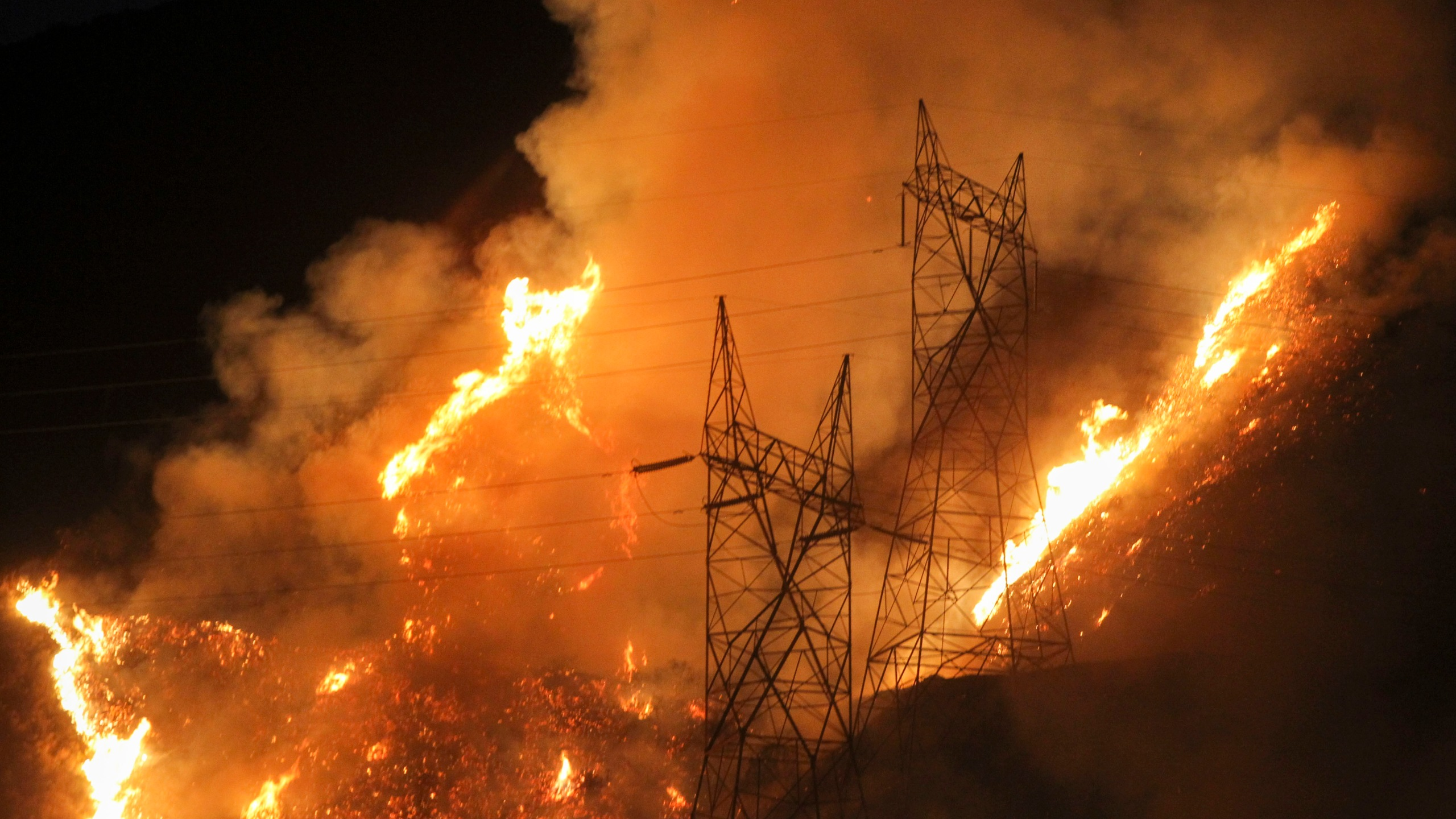 Flames flare up next to electric poles from the Blue Cut wildfire near Cajon Pass, north of San Bernardino, California on Aug. 16, 2016. (Credit: RINGO CHIU/AFP/Getty Images)