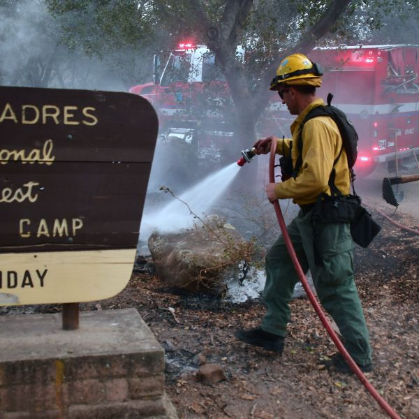 Firefighters put out burning embers from the Thomas Fire at the Los Padres National Forest north of Ojai, California on Dec. 8, 2017. (Credit: Frederic J. Brown/AFP/Getty Images)