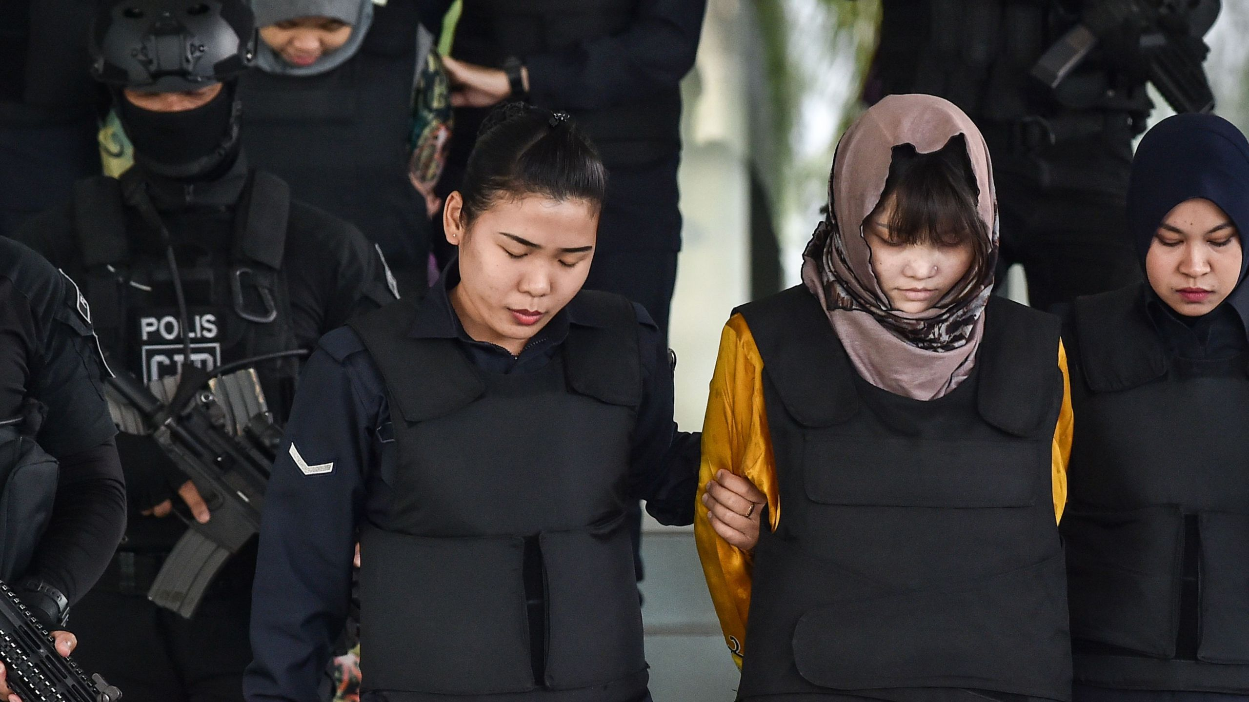 Vietnamese national Doan Thi Huong (front, second from right) and Indonesian national Siti Aisyah (back, second from left) are escorted by Malaysian police after a court session for their trial for their alleged roles in the assassination of Kim Jong Nam at the Shah Alam High Court, outside Kuala Lumpur, on June 27, 2018. (Credit: Mohd Rasfan / AFP / Getty Images)
