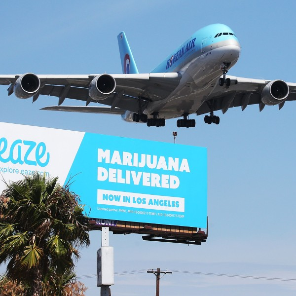 An airplane descends to land at Los Angeles International Airport above a billboard advertising the marijuana delivery service Eaze on July 12, 2018. (Credit: Mario Tama / Getty Images)
