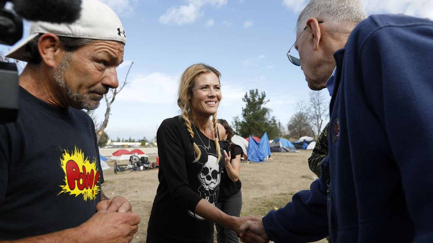 U.S. District Judge David Carter, right, greets homeless residents Frank Fabozzi, 56, and Amy Potter, 47, while surveying the homeless encampment along the Santa Ana River in Anaheim in February 2018. (Credit: Gary Coronado / Los Angeles Times)