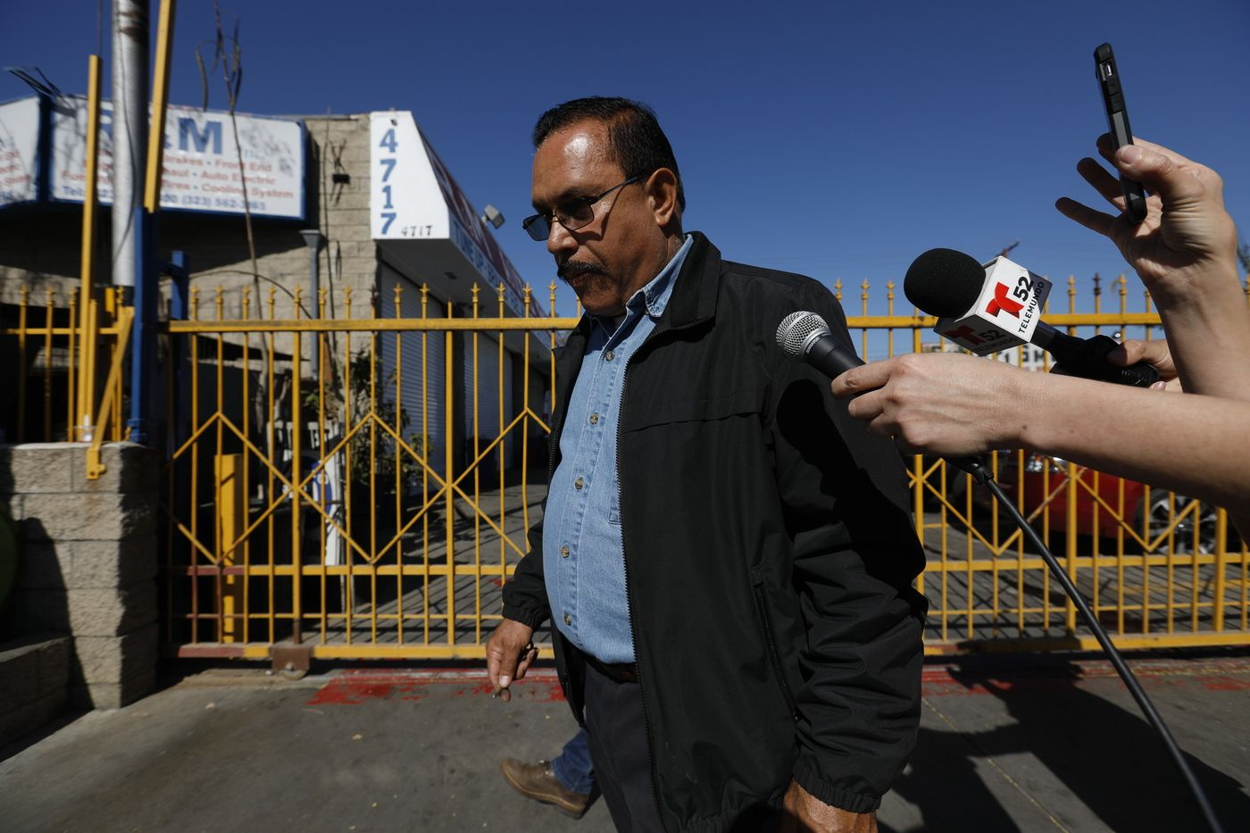Maywood Mayor Ramon Medina is asked questions by the media after investigators from the Los Angeles County District Attorney's Office removed computers and files from his auto shop on Feb. 8, 2018. (Credit: Gary Coronado / Los Angeles Times)