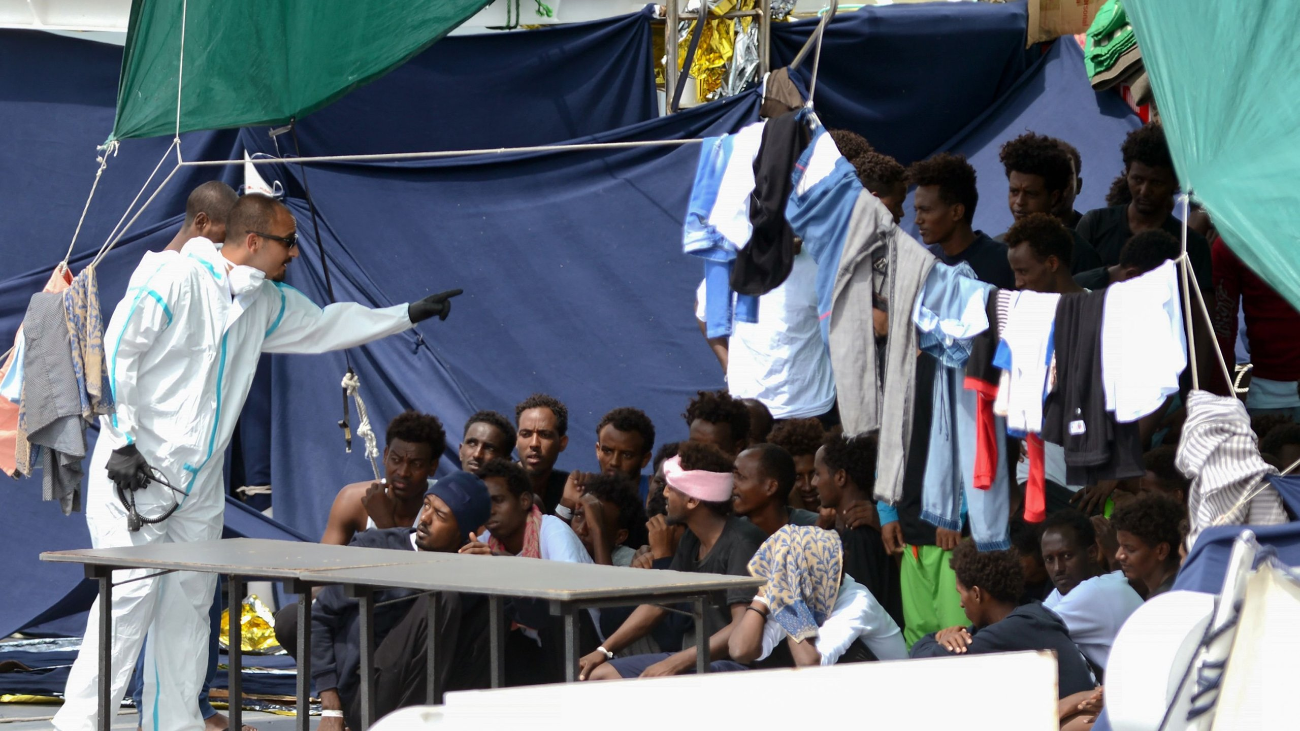 An official gestures towards migrants on the deck of the Italian Coast Guard ship Ubaldo Diciotti in the Sicilian port of Catania, on Aug. 23, 2018. (Credit: AFP/Getty Images via CNN)