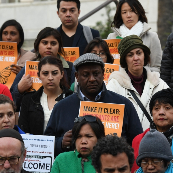 """Immigrant rights groups look on during a vigil to protest President Donald Trump's crackdown on """"sanctuary cities"""" outside Los Angeles City Hall on January 25, 2017. (MARK RALSTON/AFP/Getty Images)"""