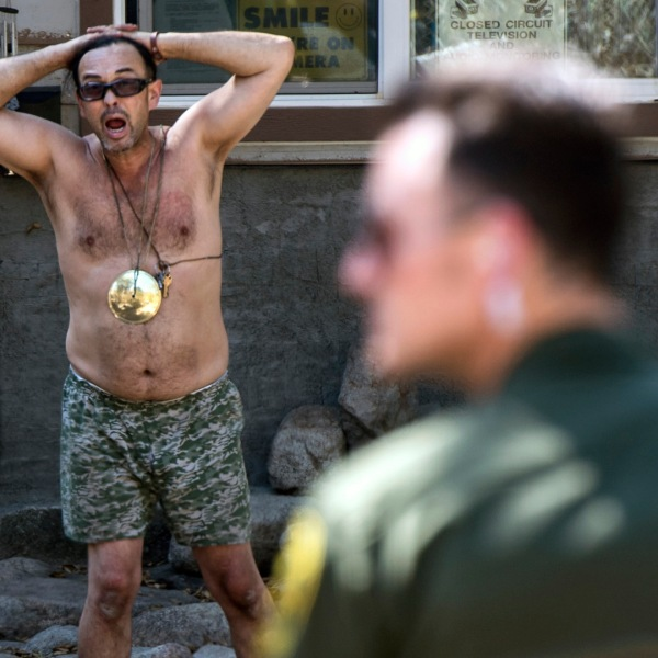 Sheriff deputies talk to Forrest Gordon Clark, a Holy Jim Canyon resident whose home was the only surviving structure in his 14 cabin area. (Credit: Mindy Schauer / Orange County Register via Getty Images)