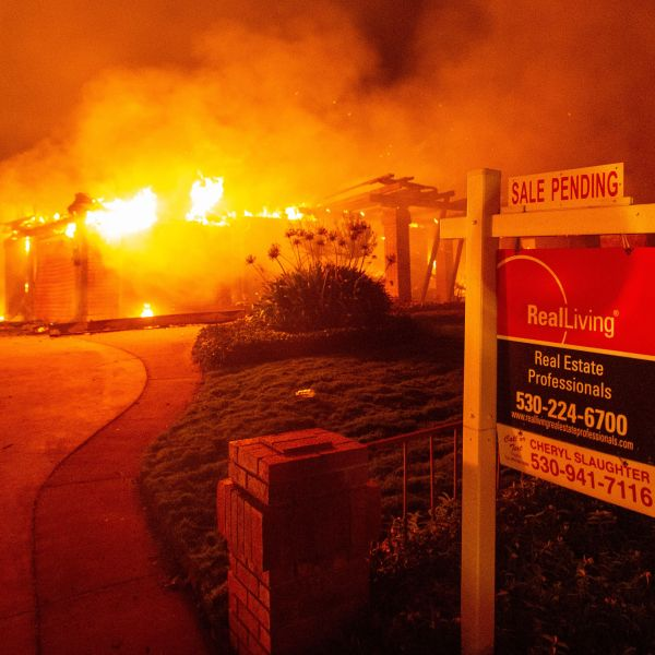 A real estate sign is seen in front of a burning home in Redding during the Carr Fire on July 27, 2018. (Credit: Josh Edelson / AFP / Getty Images)