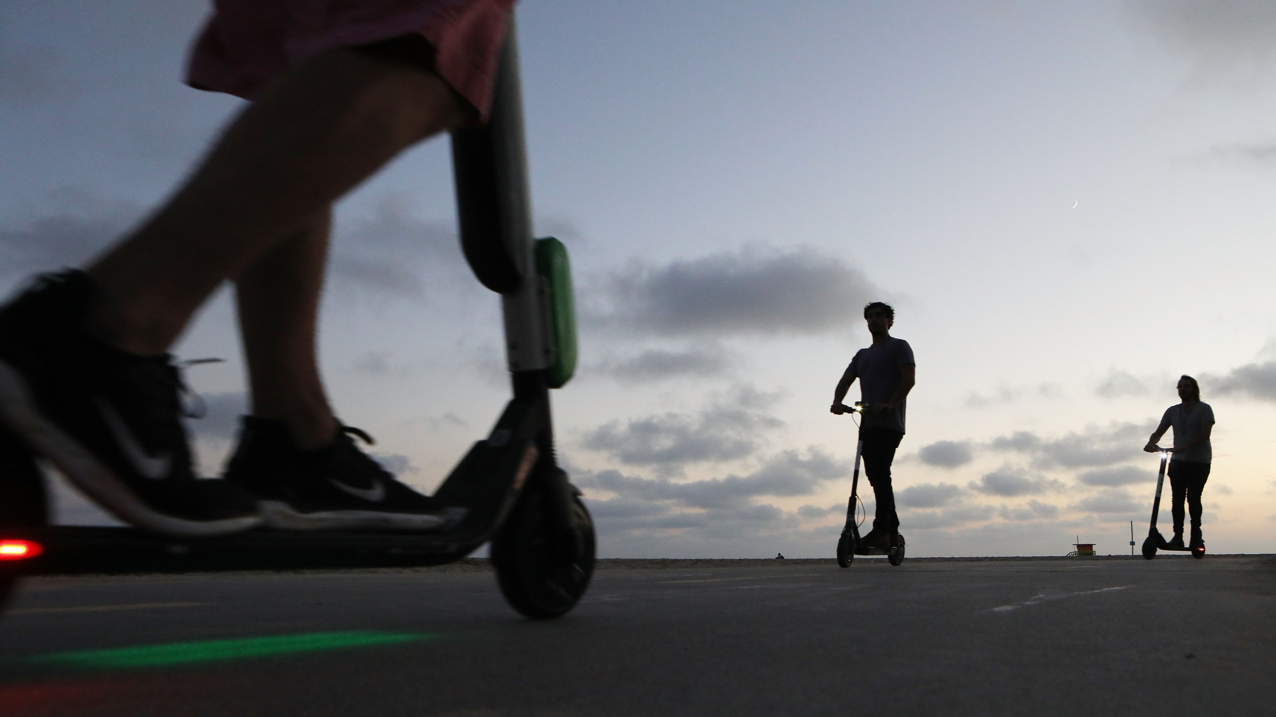 People ride shared dockless electric scooters along Venice Beach on Aug. 13, 2018. (Credit: Mario Tama/Getty Images)