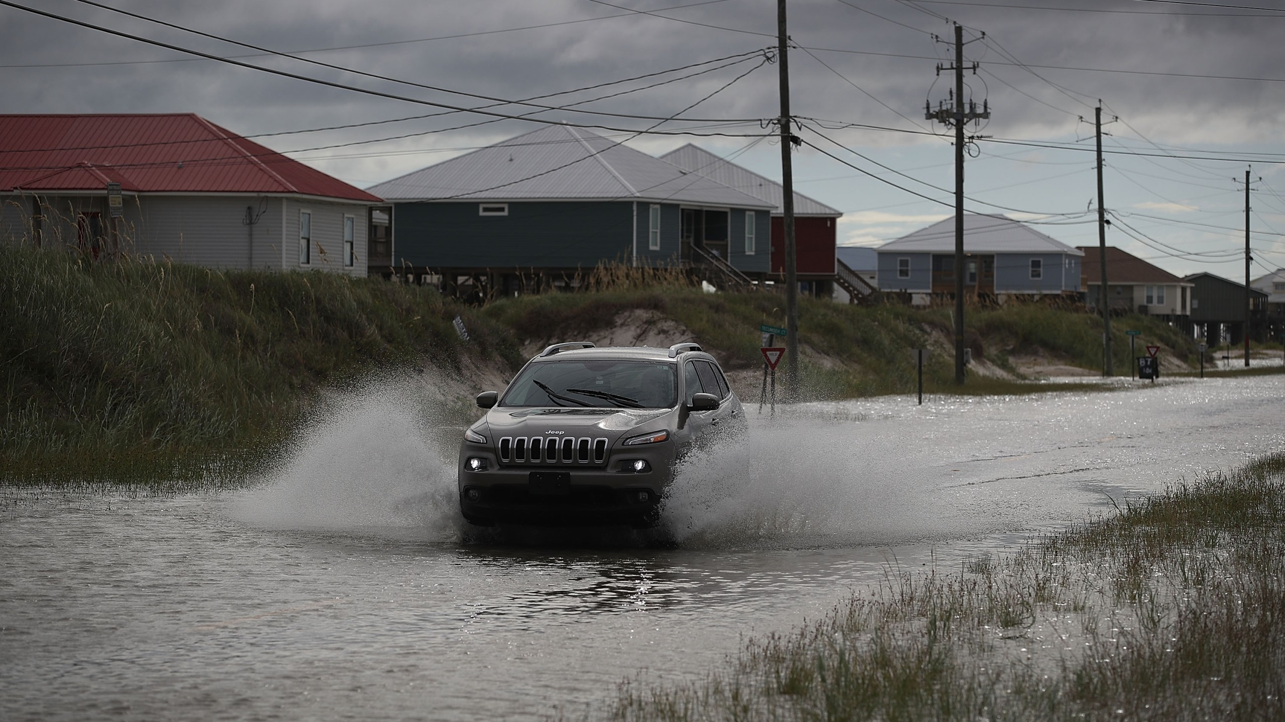 A vehicle drives along a flooded street caused by the approaching Tropical Storm Gordon on September 4, 2018 in Dauphin Island, Alabama. (Credit: Joe Raedle/Getty Images)