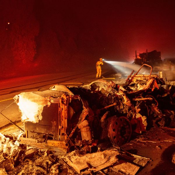 A firefighter sprays down a burned big rig truck that was abandoned along Interstate 5 as the Delta Fire tore through the region in Delta on Sept. 5, 2018. (JOSH EDELSON/AFP/Getty Images)