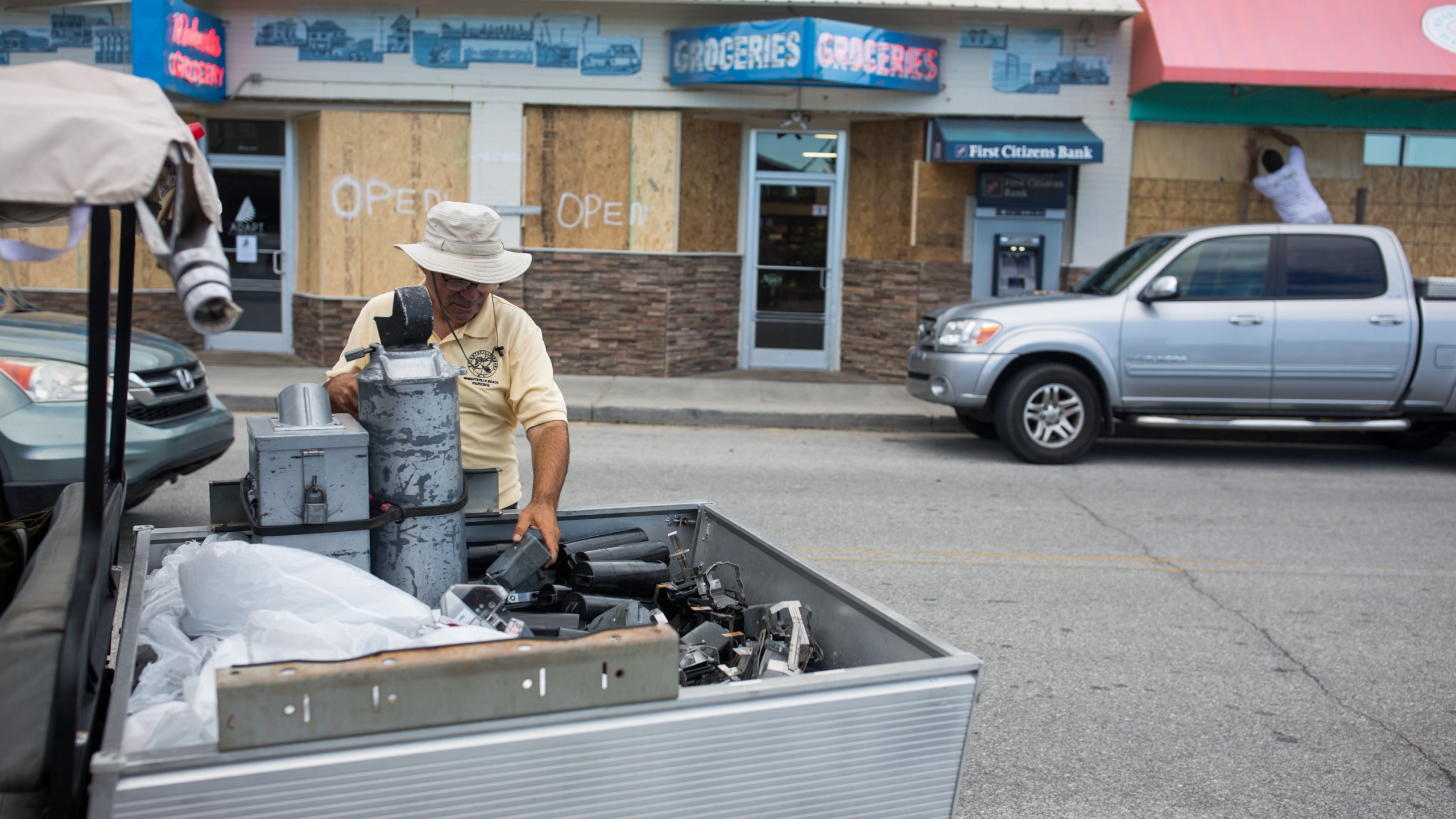 Mary Burdwood, an employee of the Wrightsville Beach Parking office removes the electronic parts of the parking meters on North Lumina Avenue in Wrightsville Beach, North Carolina on Sept. 11, 2018, removing the meters in anticipation of Hurricane Florence's high storm surge. (Credit: Logan Cyrus/AFP/Getty Images)