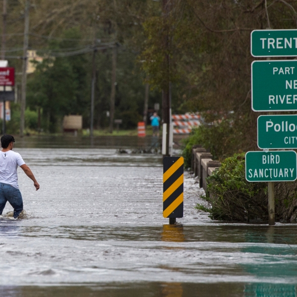 A man wades across a bridge flooded by Hurricane Florence in Pollocksville, North Carolina, on September 16, 2018. (Credit: ANDREW CABALLERO-REYNOLDS/AFP/Getty Images)