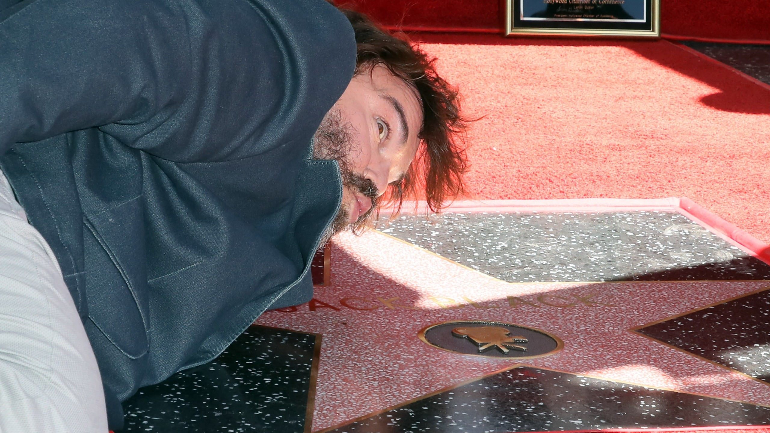 Jack Black pretends to kiss his newly-minted star on the Hollywood Walk of Fame on Sept. 18, 2018. (Credit: David Livingston/Getty Images)