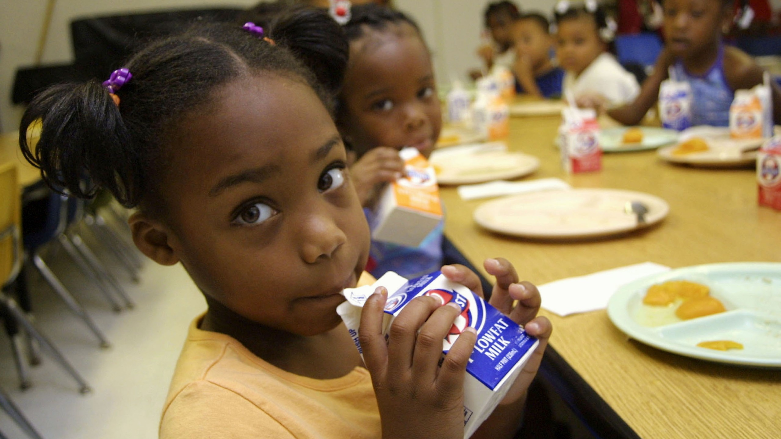 Dhaija Smith, 4, finishes her milk during breakfast with her classmates at the Brown E. Moore Head Start Center on July 22, 2003, in Shreveport, Louisiana. (Credit: Mario Villafuerte / Getty Images)