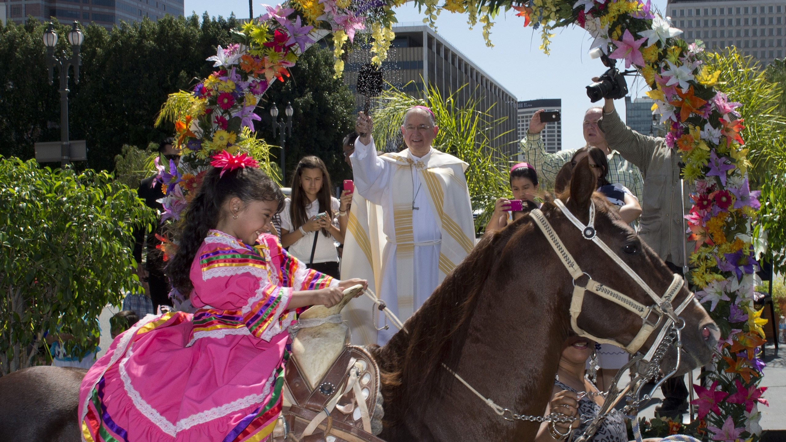Anaii Gutierrez,4, and her horse Cara de Chango receive a holy water blessing from Catholic Archbishop Jose H. Gomez during a Blessing of Animals Easter event in Los Angeles on April 4, 2015. (Credit: MARK RALSTON/AFP/Getty Images)