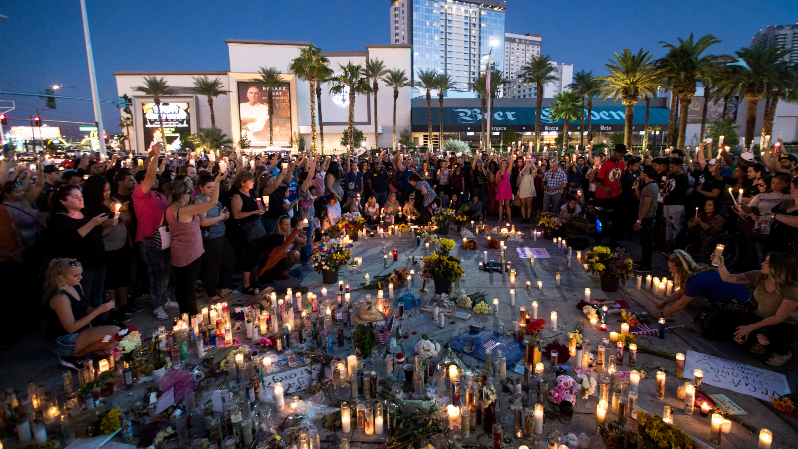 Mourners hold their candles in the air during a moment of silence during a vigil to mark one week since the mass shooting at the Route 91 Harvest country music festival, on the corner of Sahara Avenue and Las Vegas Boulevard at the north end of the Las Vegas Strip, on Oct. 8, 2017, in Las Vegas. (Credit: Drew Angerer/Getty Images)