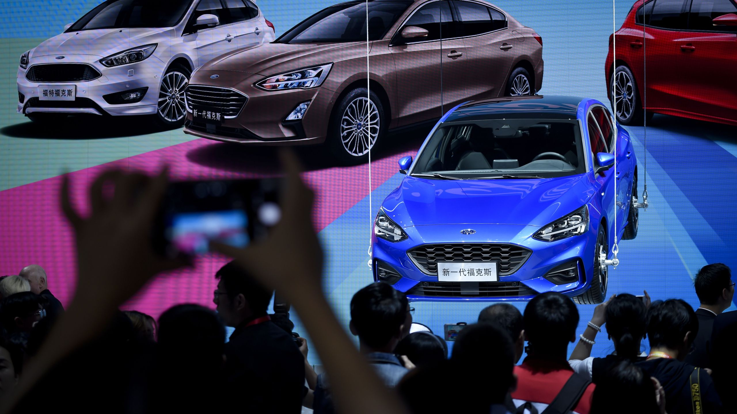 Visitors look at a display for the new Ford Focus at the Beijing auto show in Beijing on April 25, 2018. (Credit: WANG ZHAO/AFP/Getty Images)