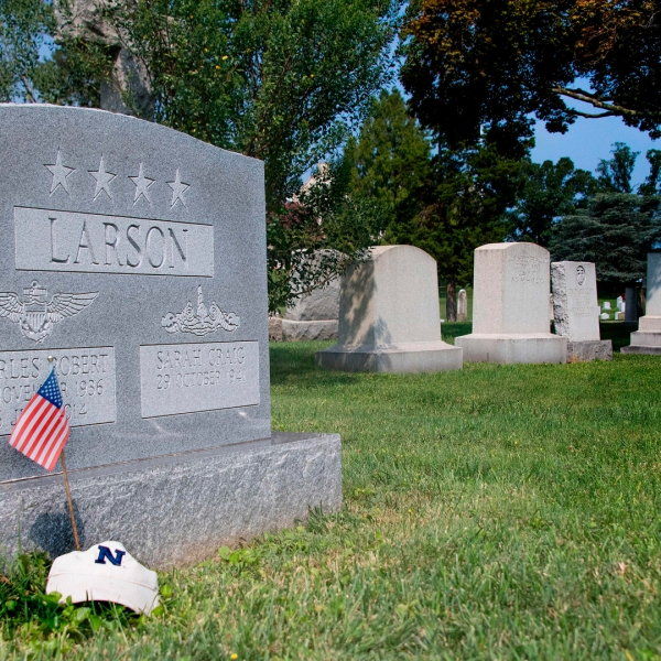 "A flag is placed at the base of the tombstone of U.S. Navy Adm. Charles ""Chuck"" Larson at the U.S. Naval Academy in Annapolis, Maryland, on Aug. 24, 2018, near where Sen. John McCain will be laid to rest. (Credit: JIM WATSON/AFP/Getty Images)"