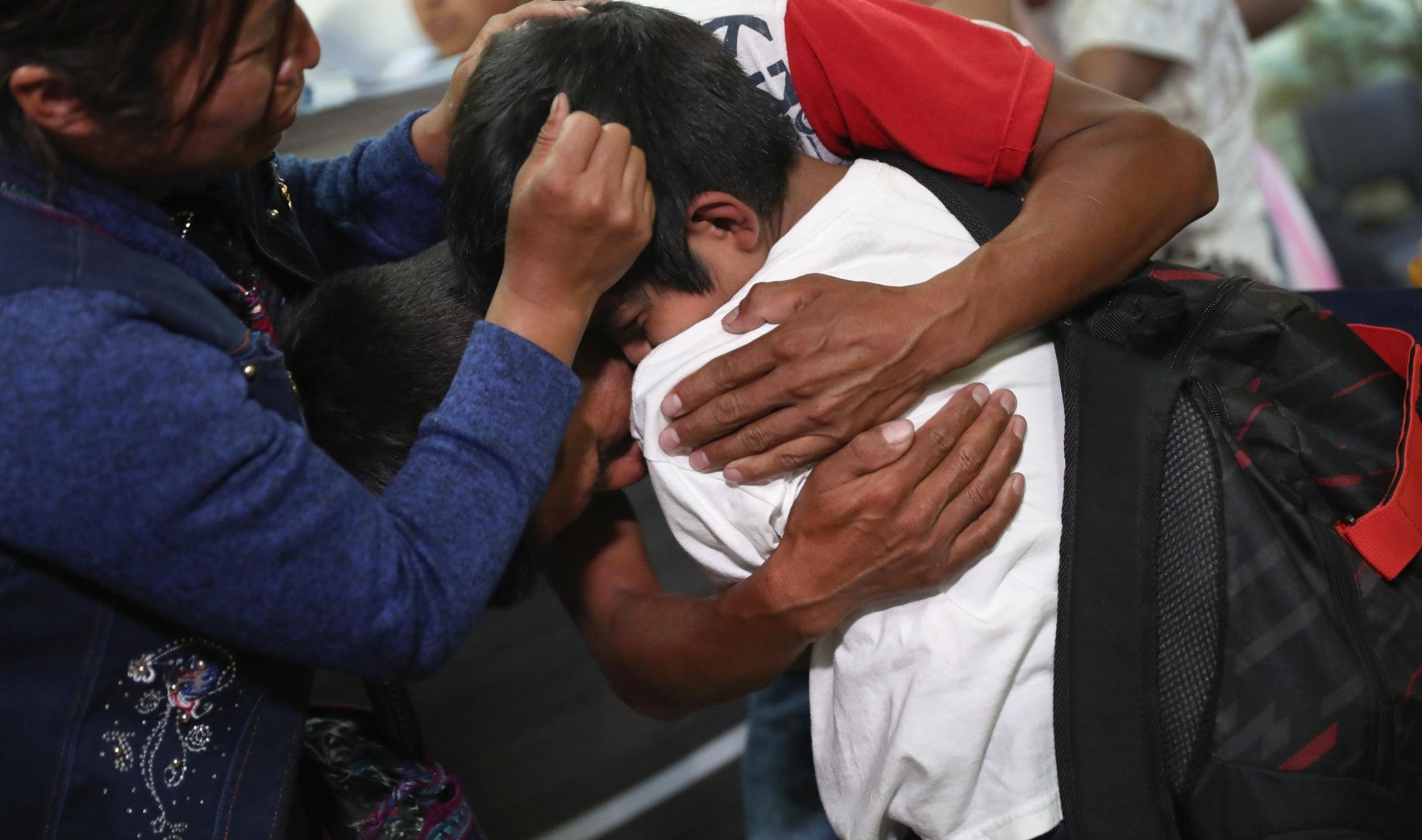 Parents embrace their son for the first time in months on Aug. 7, 2018, in Guatemala City, Guatemala. (Credit: John Moore / Getty Images)
