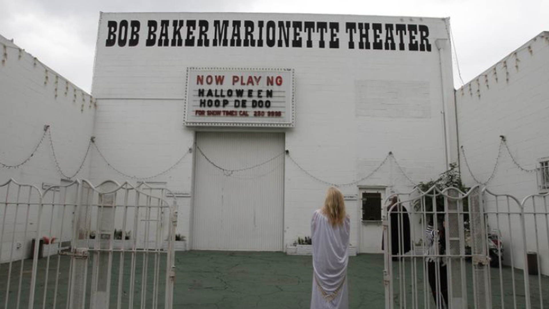 Suzy Vecchio stands outside the Bob Baker Marionette Theater after seeing a puppet show in this undated photo. The theater's lease on the building will end soon, and the building owner is planning to construct new apartments and retail space. (Credit: Allen J. Schaben / Los Angeles Times)