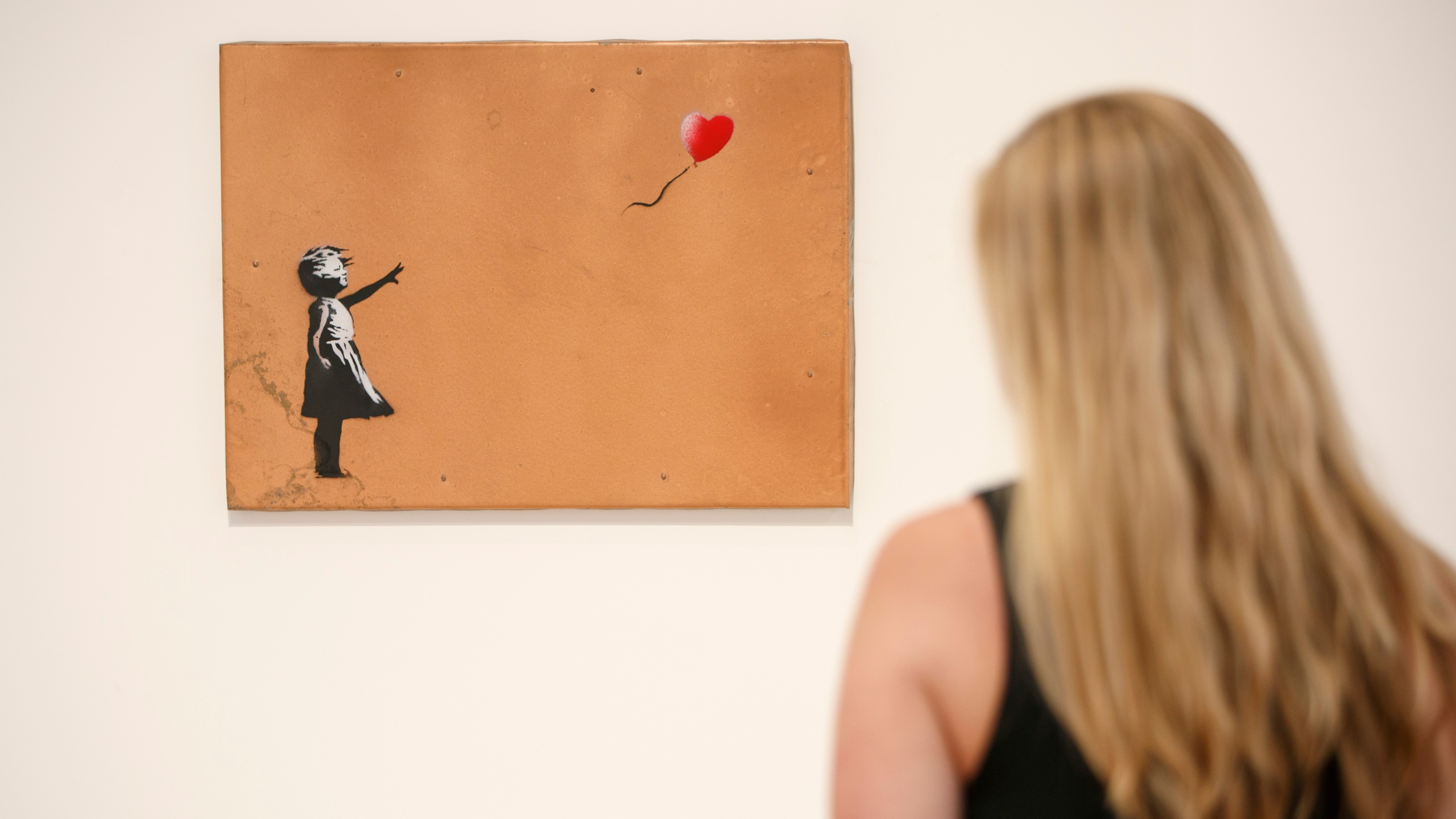 A gallery assistant poses with 'Girl with Balloon' 2006 artwork by Banksy at Lazinc Gallery in London on July 11, 2018. - The exhibition opens to the public on July 12, 2018. (Credit: TOLGA AKMEN/AFP/Getty Images)