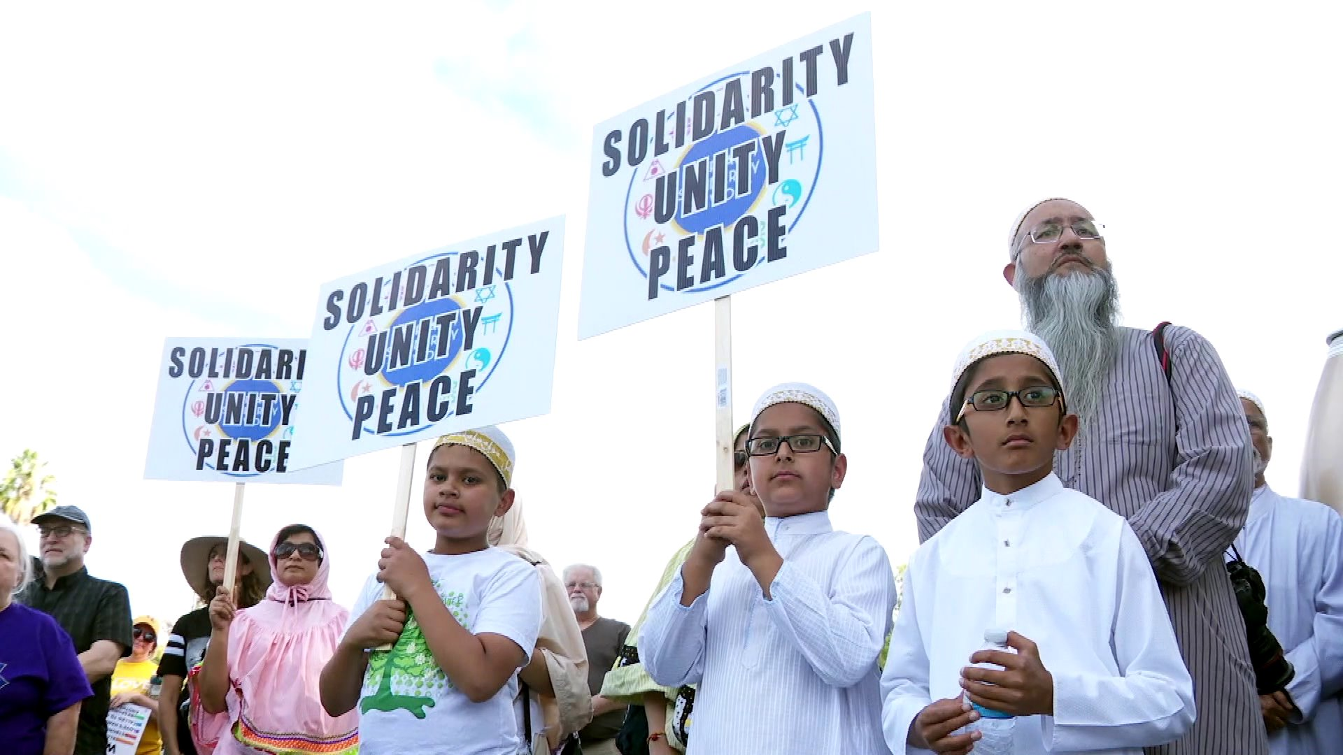 Children are seen holding signs at an interfaith march in Woodland Hills on Oct. 28, 2018, a day after a man launched a deadly attack on a synagogue in Pittsburgh. (Credit: KTLA)