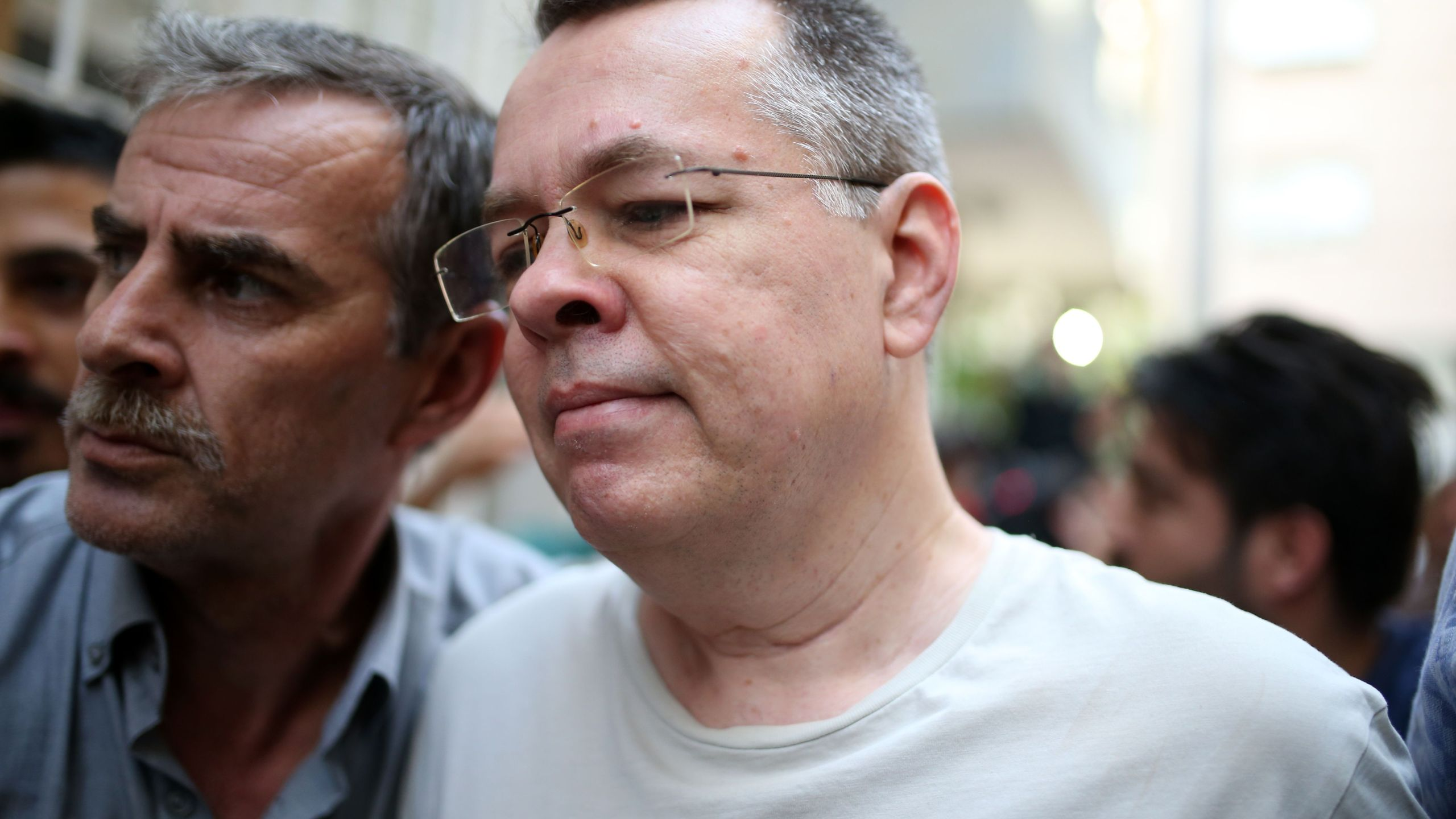 Pastor Andrew Craig Brunson (R), escorted by Turkish plain clothes police officers as he arrives at his house on July 25, 2018 in Izmir. (Credit: STRINGER/AFP/Getty Images)