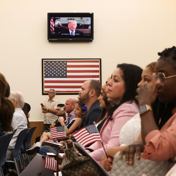 People listen to a taped broadcast of President Donald Trump as they participate in a ceremony to become American citizens during a U.S. Citizenship and Immigration Services naturalization ceremony at the Miami Field Office on Aug. 17, 2018 in Miami, Florida. (Credit: Joe Raedle/Getty Images)
