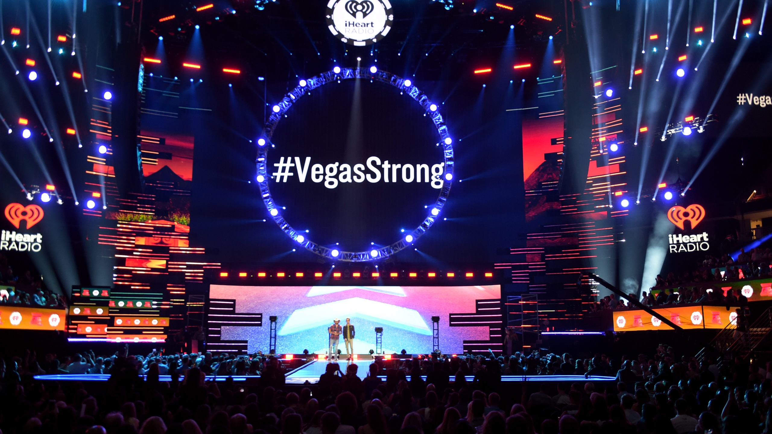 '#VegasStrong' is projected on a video screen while Jason Aldean (L) and Bobby Bones speak onstage during the 2018 iHeartRadio Music Festival at T-Mobile Arena on September 21, 2018 in Las Vegas, Nevada. (Credit: Kevin Winter/Getty Images for iHeartMedia)