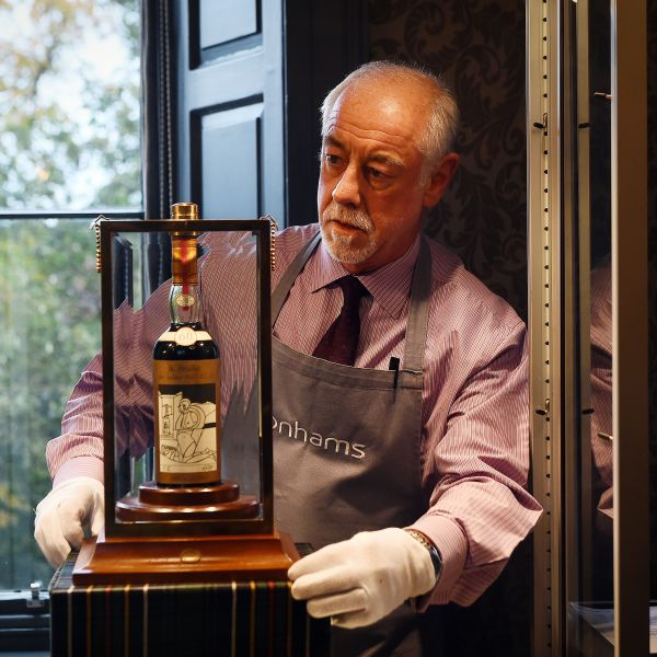 A Bonhams porter shows the bottle of Macallan Valerio Adamai 1926 whisky which sold for a world record sale price of $1.1 million at an auction in Edinburgh, Scotland, on Oct. 3, 2018. (Credit: ANDY BUCHANAN/AFP/Getty Images)