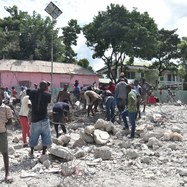 Haitian people collect metal on Oct. 7, 2018 in Gros Morne, Haiti from a destroyed auditorium after an earthquake struck north of Haiti on Oct. 6, 2018. (Credit: HECTOR RETAMAL/AFP/Getty Images)