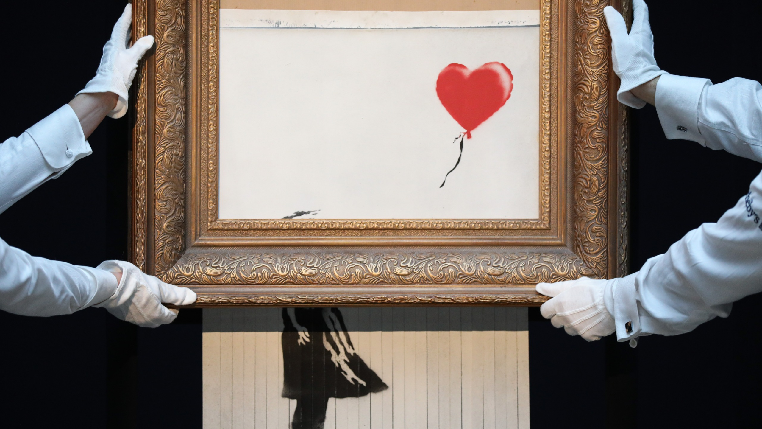 "Sotheby's unveils Banksy's newly-titled ""Love is in the Bin"" at Sotheby's in London on Oct. 12, 2018. Originally titled ""Girl with Balloon,"" the canvas passed through a hidden shredder seconds after the hammer fell at Sotheby's London Contemporary Art Evening Sale on Oct. 5, 2018, making it the first artwork in history to have been created live during an auction. (Credit: Tristan Fewings / Getty Images for Sotheby's)"