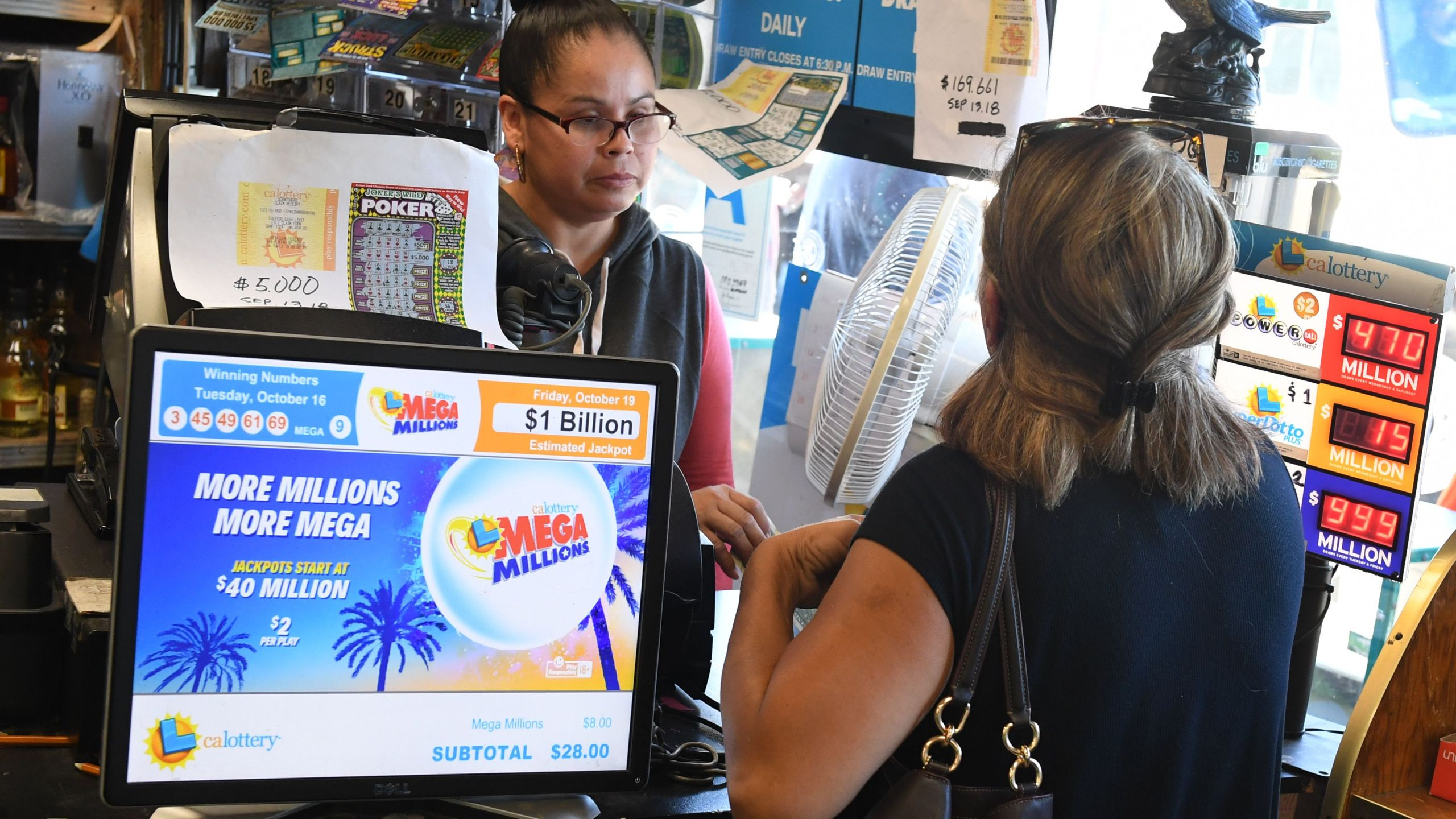 Customers buy Mega Millions tickets hours before the draw of the $1 billion jackpot at the Bluebird Liquor store in Torrance on Oct. 19, 2018. (Credit: MARK RALSTON/AFP/Getty Images)