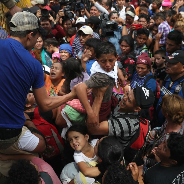 Children in a migrant caravan are lifted over a gate at the Guatemala-Mexico border on Oct. 19, 2018, in Ciudad Tecun Uman, Guatemala. (Credit: John Moore / Getty Images)
