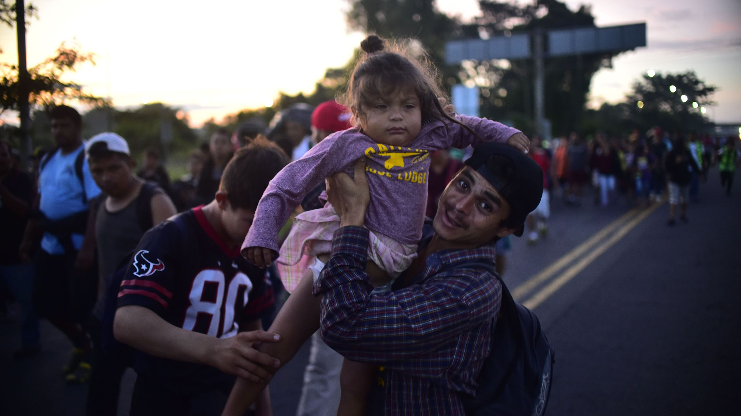A Honduran migrant holds up a baby as they take part in a caravan heading to the U.S. on the road linking Ciudad Hidalgo and Tapachula, Chiapas state, Mexico, on Oct. 21, 2018. (Credit: PEDRO PARDO/AFP/Getty Images)