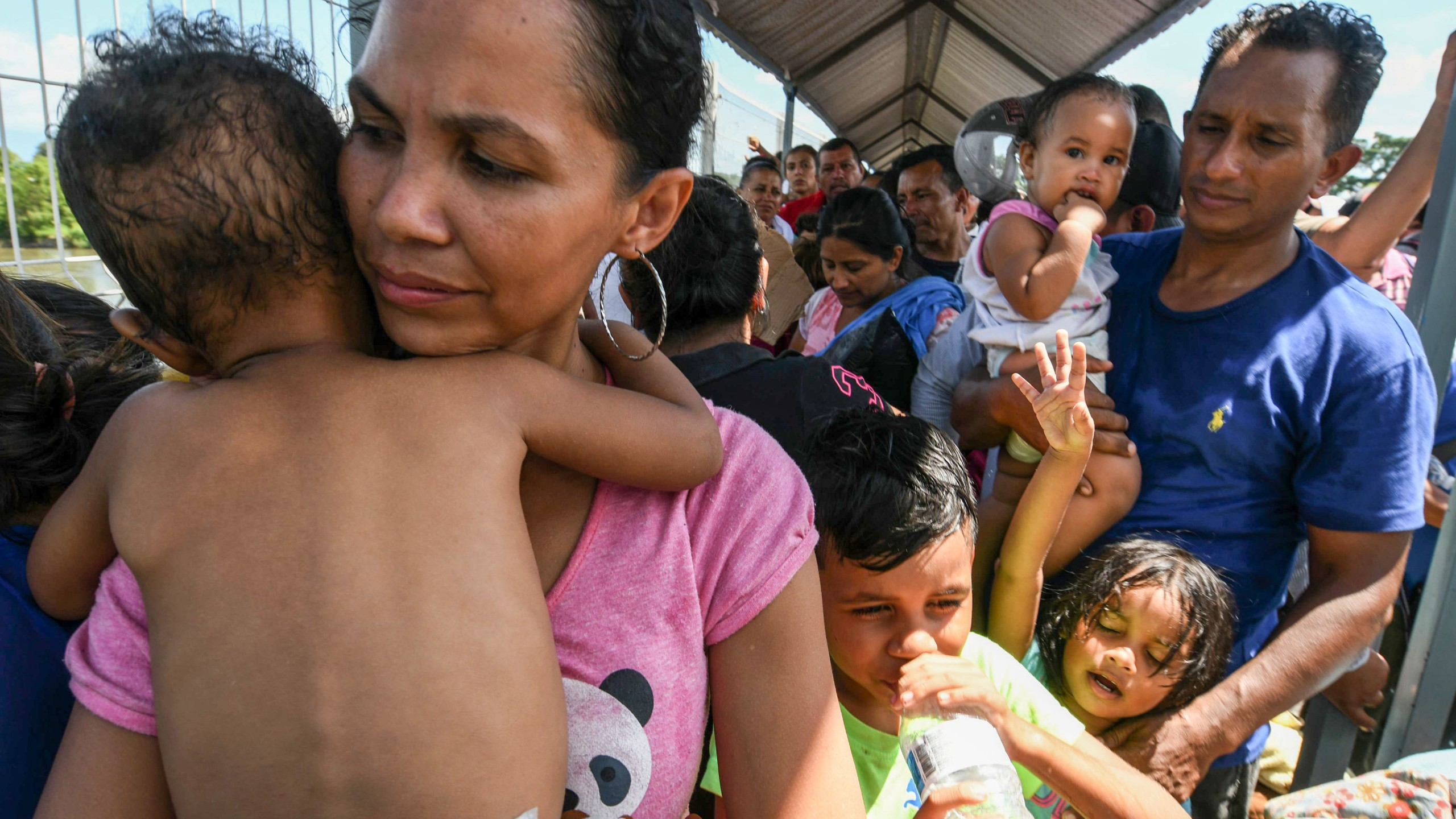 A Honduran migrant couple and their five children who are taking part in a caravan heading to the U.S. wait to cross the border from Ciudad Tecun Uman in Guatemala, to Ciudad Hidalgo, Mexico, on Oct. 22, 2018. (Credit: ORLANDO SIERRA/AFP/Getty Images)
