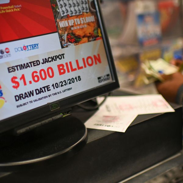 A woman buys Mega Millions tickets hours before the draw of the $1.6 billion jackpot, at a liquor store in downtown Washington D.C., on Oct. 23, 2018. (Credit: ERIC BARADAT/AFP/Getty Images)