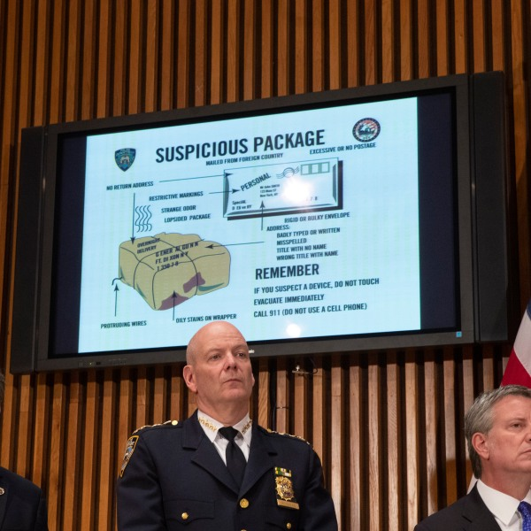 A monitor displays information about suspicious packages as NYPD Chief of Department Terence Monahan, center, and New York City Mayor Bill de Blasio, right, look on during a press conference at NYPD headquarters regarding the recent package bombings, Oct. 25, 2018. (Credit: Drew Angerer / Getty Images)