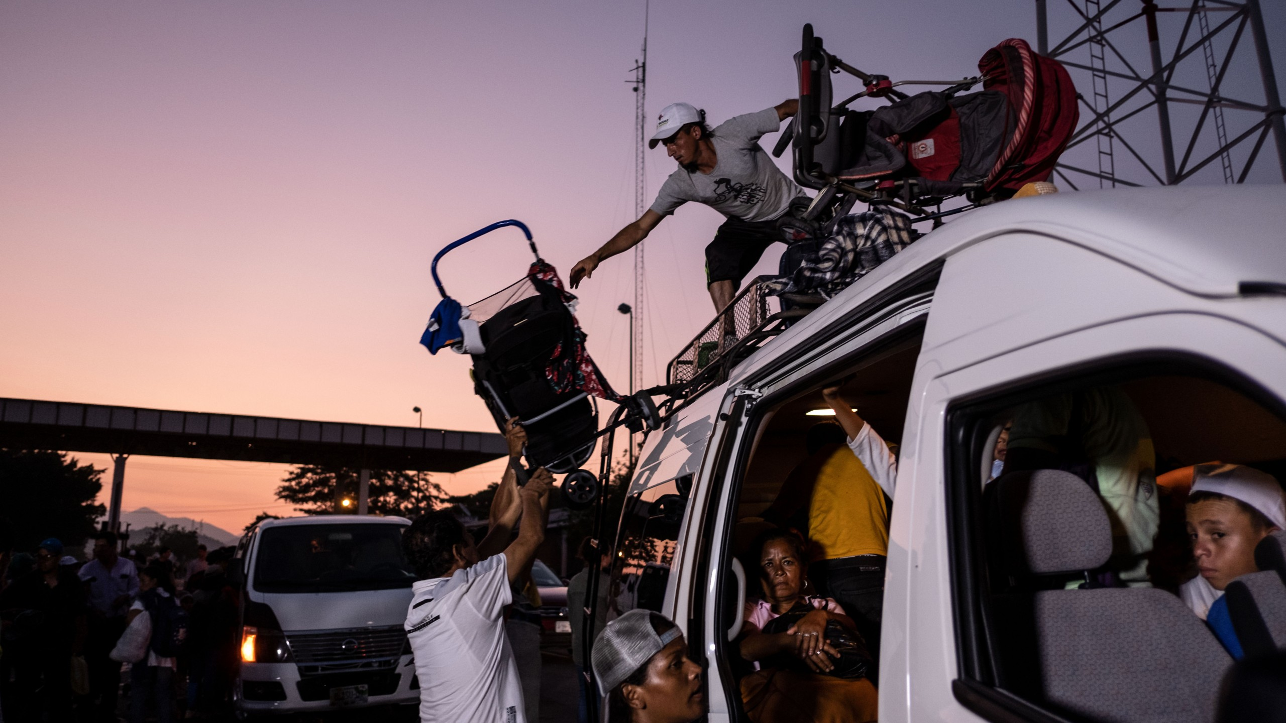 Honduran migrants heading in a caravan to the US, upload their baby strollers on a van, near Pijijiapan, southern Mexico on October 26, 2018. (Credit: Guillermo Arias/AFP/Getty Images)