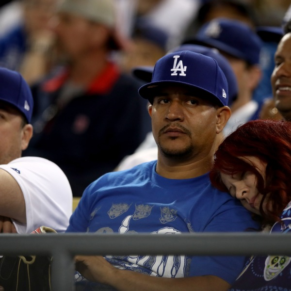 A fan rests during the 17th inning in Game 3 of the 2018 World Series between the Los Angeles Dodgers and the Boston Red Sox at Dodger Stadium on Oct. 26, 2018. (Credit: Ezra Shaw/Getty Images)