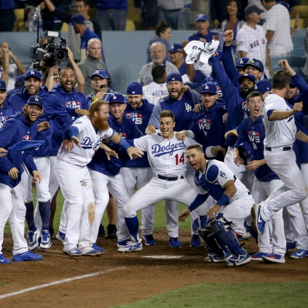 The Los Angeles Dodgers wait to congratulate Max Muncy #13 at home plate after his 18th inning walk-off home run to defeat the the Boston Red Sox 3-2 in Game 3 of the 2018 World Series at Dodger Stadium on Oct. 26, 2018. (Credit: Jeff Gross/Getty Images)
