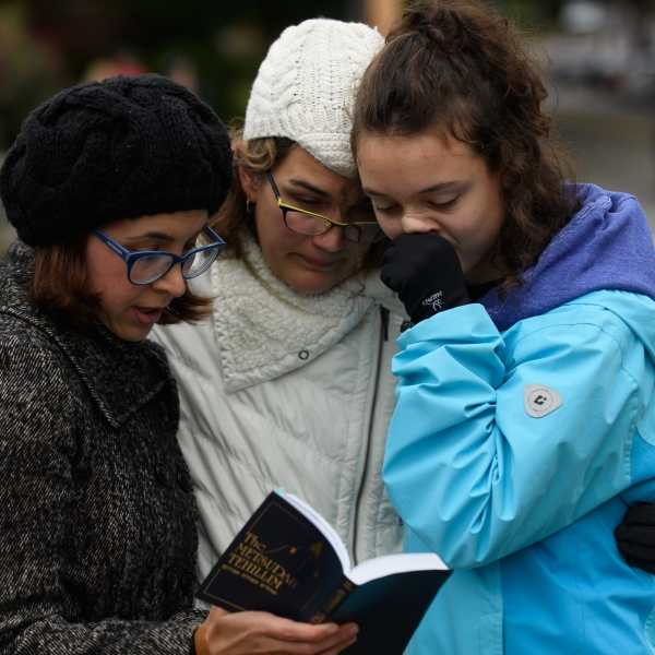 Tammy Hepps, Kate Rothstein and her daughter, Simone Rothstein, 16, pray from a prayerbook a block away from the site of a mass shooting at the Tree of Life Synagogue in the Squirrel Hill neighborhood on Oct. 27, 2018 in Pittsburgh, Pennsylvania. (Credit: Jeff Swensen/Getty Images)