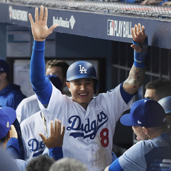 Manny Machado #8 of the Los Angeles Dodgers celebrates with teammates in the dugout after scoring on a three-run home run hit by Yasiel Puig #66 in the sixth inning of Game 4 of the 2018 World Series against the Boston Red Sox at Dodger Stadium on Oct. 27, 2018 in Los Angeles. (Credit: Harry How/Getty Images)