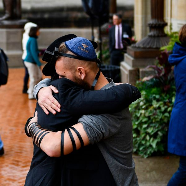 People hug as they arrive for a vigil following a mass shooting at the Tree of Life synagogue at the Allegheny County Soldiers Memorial on Oct. 28, 2018, in Pittsburgh, Pennsylvania.(Credit: BRENDAN SMIALOWSKI/AFP/Getty Images)