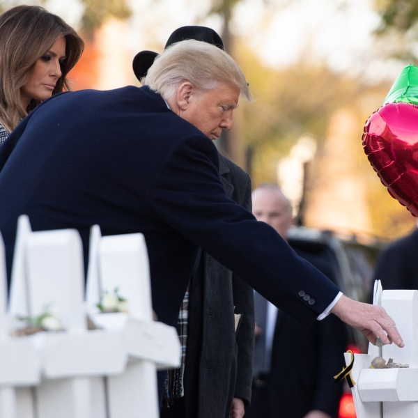 Donald Trump and First Lady Melania Trump, alongside Rabbi Jeffrey Myers, place stones and flowers on a memorial as they pay their respects at the Tree of Life Synagogue shooting victims in Pittsburgh on Oct. 30, 2018. (Credit: Saul Loeb/AFP/Getty Images)