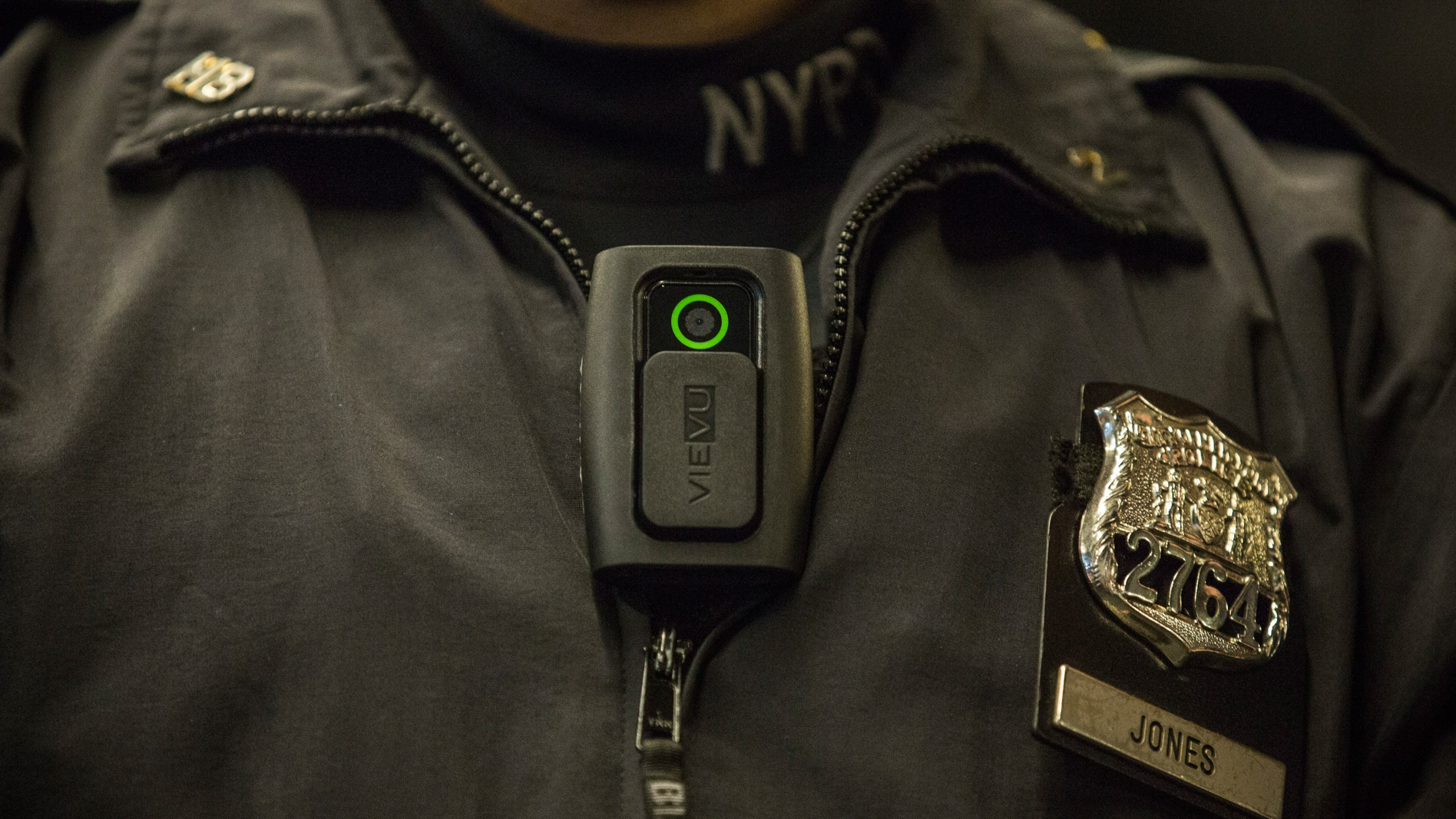 New York Police Department Officer Joshua Jones demonstrates how to use and operate a body camera during a press conference on Dec. 3, 2014 in New York City. (Credit: Andrew Burton/Getty Images)
